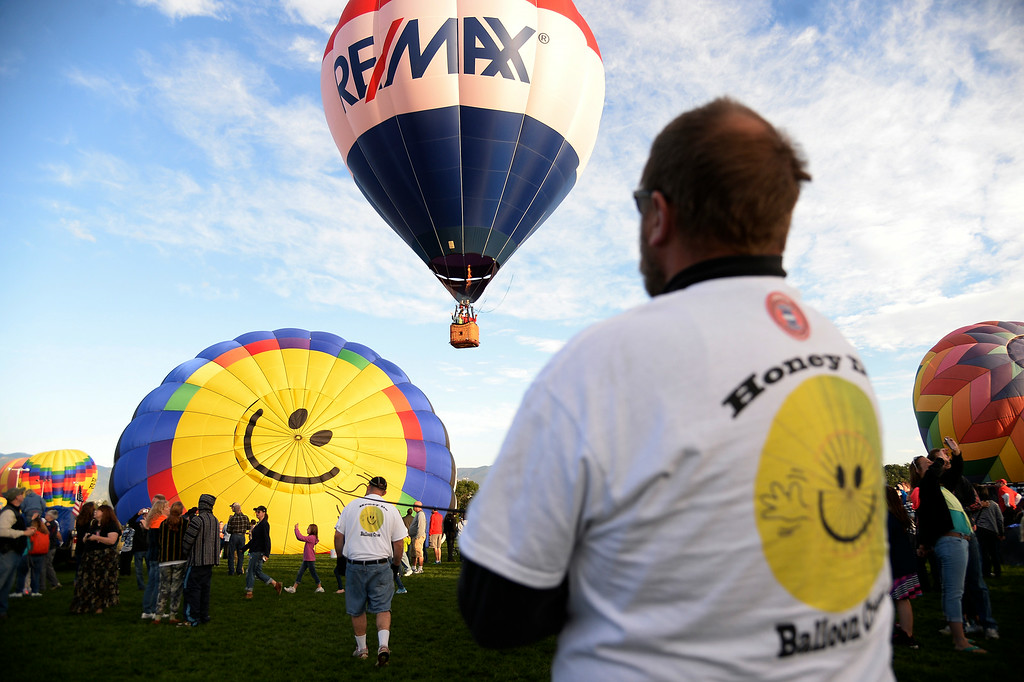 ". Paul Lavergne hold the line to ""Honey Do\"" as hundreds of balloon enthusiasts gather to watch the launch of The 2014 Colorado Balloon Classic t Memorial Park. \""Honey Do\"" is owned by Linda Walker and Piloted by Bill Walker of New Mexico. This is the last year this balloon festival will be held in Colorado Springs. (Photo by John Leyba/The Denver Post)"