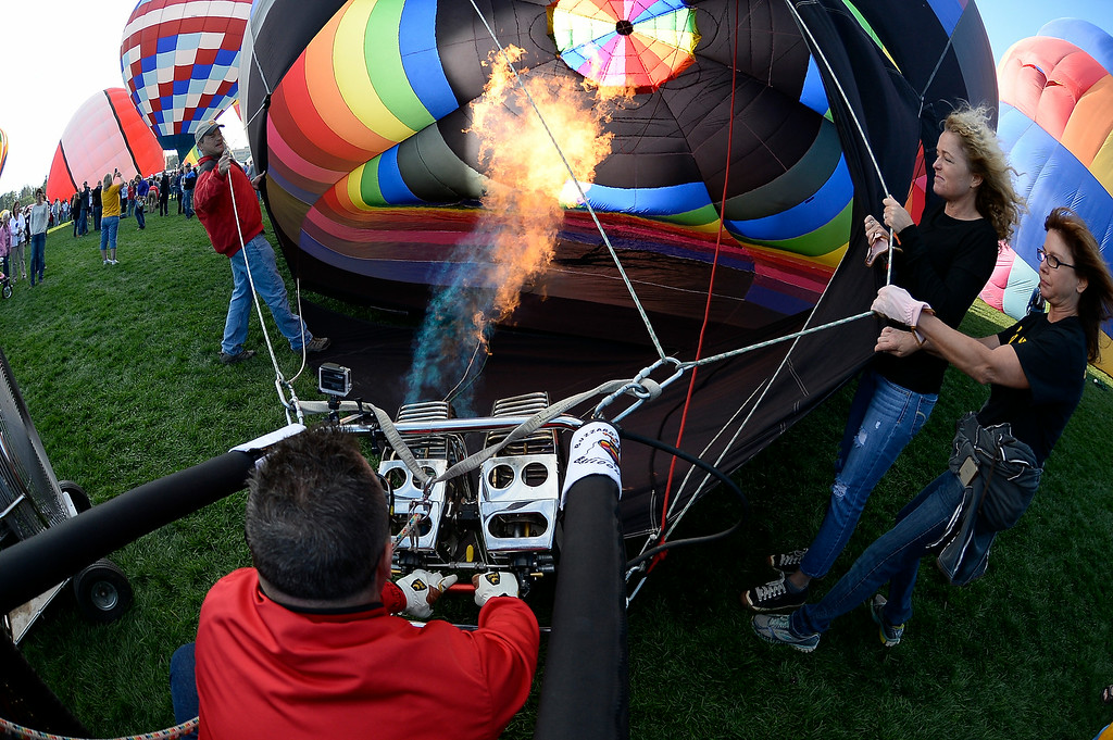 ". Earl Buzzard of ""Buzzards Roost\"" balloon fills it up with hot air as they prepare to take flight in front of hundreds of balloon enthusiasts gather to watch the launch of The 2014 Colorado Balloon Classic.   (Photo by John Leyba/The Denver Post)"