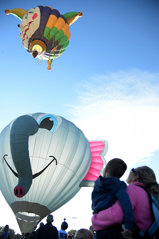 . Chelsie Barrett holds Jaxon, 4, as they watch balloons lift up to the sky while joining hundreds of balloon enthusiasts gather to watch the launch of The 2014 Colorado Balloon Classic  (Photo by John Leyba/The Denver Post)
