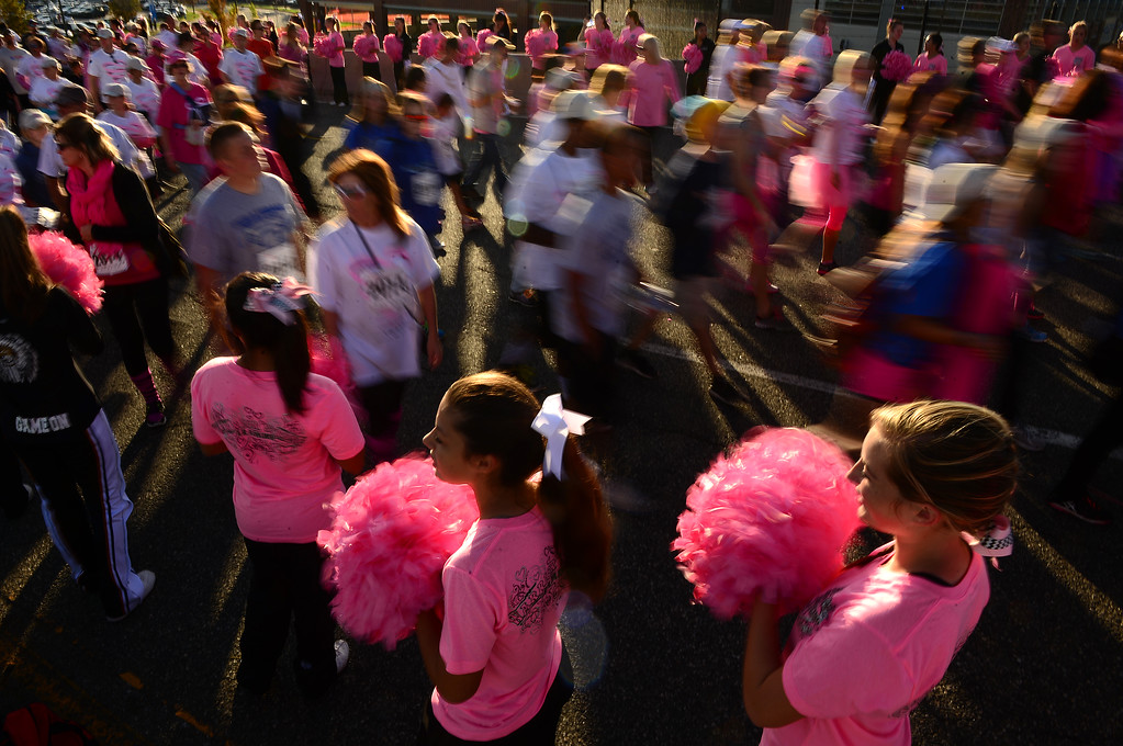 . Cheerleaders from Arapahoe High School cheer on runners and walkers at the start of the 5K inspiration run of the 22nd annual Susan G. Komen Colorado Race for the Cure in Denver, CO on September 28, 2014.  Thousands took part in the annual race which started and finished on the Auraria Parkway near the Pepsi Center.  Breast cancer remains the most common form of cancer among women living in the United States.  In Colorado 1 in 7 women will be diagnosed with breast cancer in their lifetime.  Events like Race for the Cure help fund grants to community organizations who provide breast health services to those diagnosed.   (Photo By Helen H. Richardson/ The Denver Post)