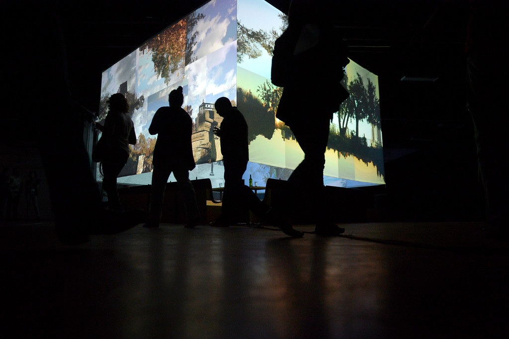 . Patrons watch films as they are projected on a cube containing the dining area during an evening at Monkey Town at 35th and Larimer. Patrons enjoy a five-course meal at Monkey Town on Sunday, March 9, 2014. (Photo By AAron Ontiveroz/ The Denver Post)