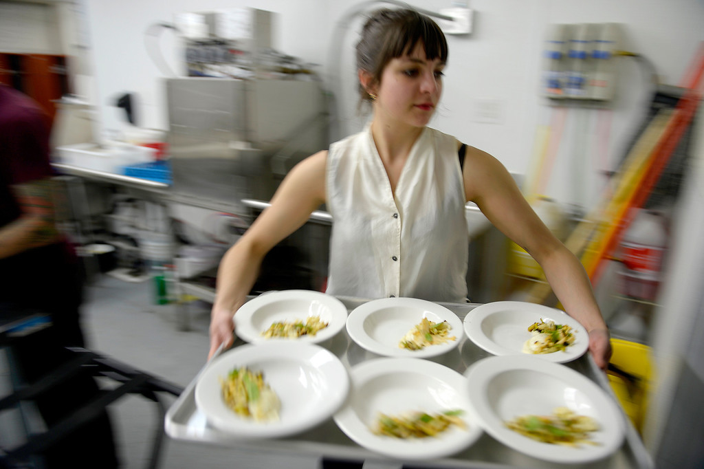. Server Katarina King carries a tray of slow-cooked eggs, cauliflower, leek and olive during an evening at Monkey Town at 35th and Larimer. Patrons enjoy a five-course meal at Monkey Town on Sunday, March 9, 2014. (Photo By AAron Ontiveroz/ The Denver Post)