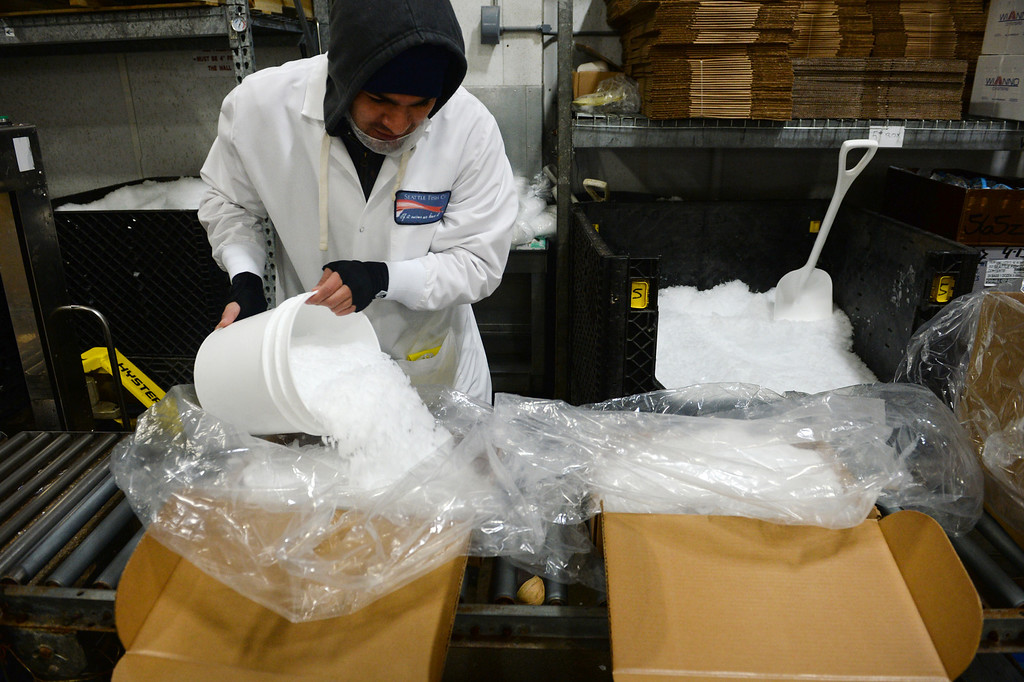 . Daniel Ravelo puts ice inside of boxes containing processed fresh fish to be delivered to local restaurants in Denver  at Seattle Fish Company in Denver on April 17, 2014.  The company processed 10 million pounds of fish last year at their facility. (Photo By Helen H. Richardson/ The Denver Post)