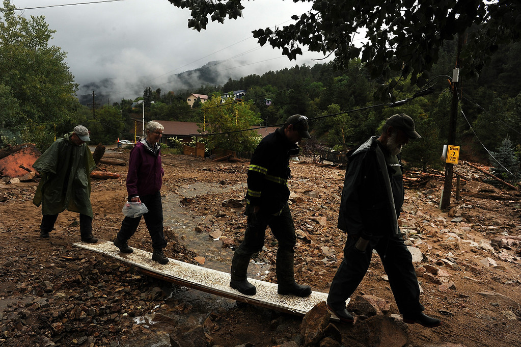 . Jamestown resident Leon Hill, right, makes his  way up town on boards that cover debris  with other residents along James Canyon drive in Jamestown, CO on September 15, 2013.   The town has been completely destroyed from the recent floods.   A dozen or so residents stayed as most of the town was evacuated by helicopters. (Photo By Helen H. Richardson/ The Denver Post)