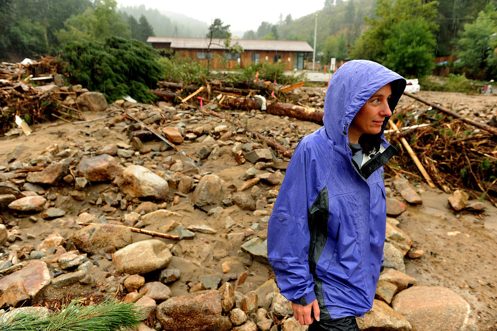 . Jamestown mayor Tara Schoedinger, with rain continuing to fall, stands in massive debris along Main Street  in Jamestown, CO on September 15, 2013.   This area was used as a landing zone for helicopters during rescues of residents of the town.   A dozen or so residents stayed as most of the town was evacuated by those helicopters. The town has no infrastructure or running water.  Some parts of town amazingly enough have electricity.  (Photo By Helen H. Richardson/ The Denver Post)