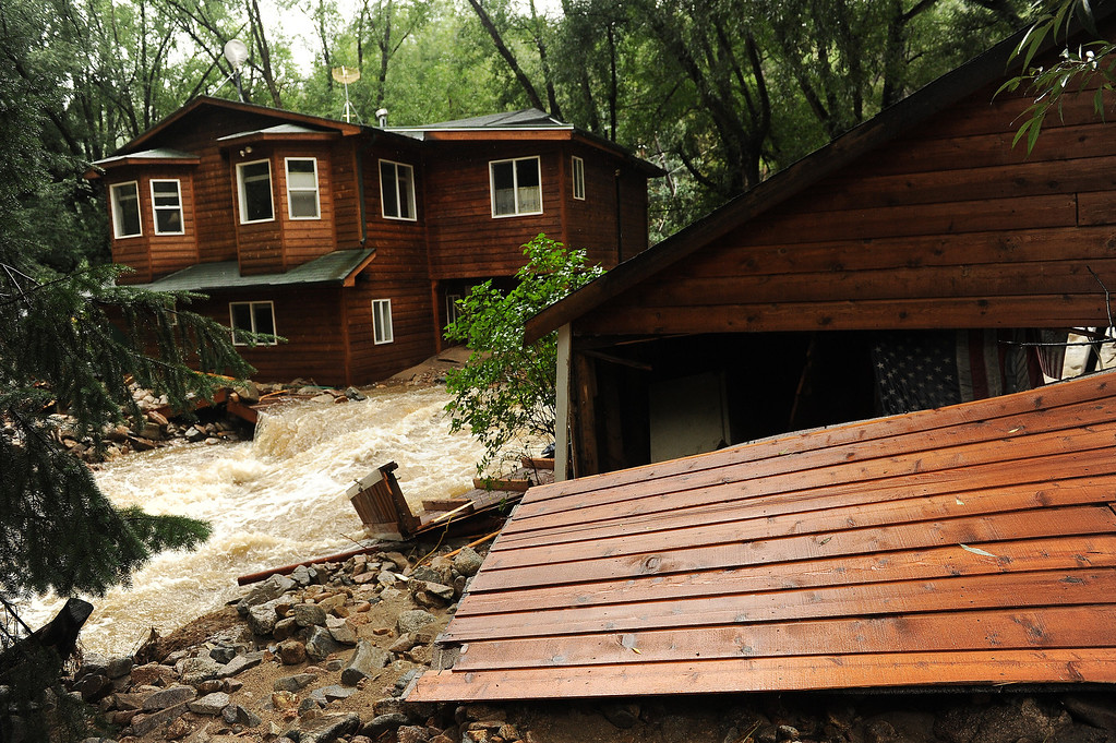 . A house is surrounded by raging water in what used to be the resident\'s back yard in Jamestown, CO on September 15, 2013.  People in the town say the the Little Jim Creek which used to flow quietly through town has changed course and is tearing apart properties and houses as it continues to rage. (Photo By Helen H. Richardson/ The Denver Post)