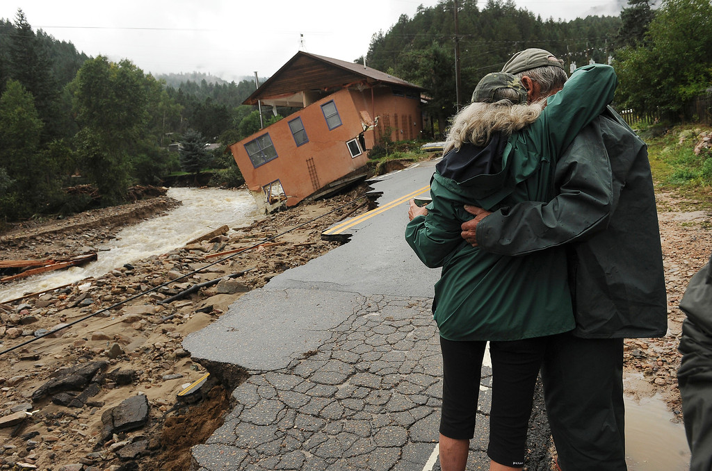 . Jamestown resident  Colleen Williams gives her neighbor Leon Hill, right,  a hug early in the morning along James Canyon drive in Jamestown, CO on September 15, 2013.   The town has been completely destroyed from the recent floods.   A dozen or so residents stayed as most of the town was evacuated by helicopters. (Photo By Helen H. Richardson/ The Denver Post)