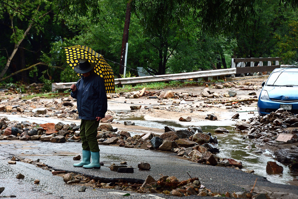 . June Hill, with a bright umbrella in hand to shield her from the falling rain, stands amidst the debris on Main street  in Jamestown, CO on September 15, 2013.   The town has been completely destroyed from the recent floods. June and her husband did not lose their house to the floods and currently and amazingly enough have electricity.  (Photo By Helen H. Richardson/ The Denver Post)
