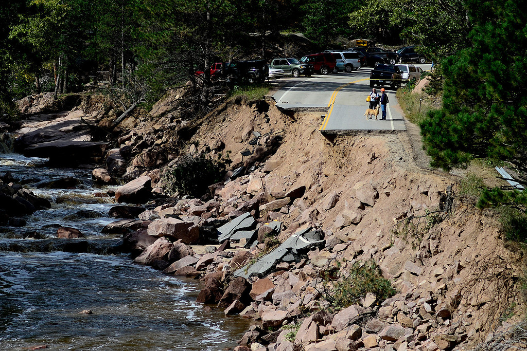 . PINEWOOD SPRINGS, CO - SEPTEMBER 22: People park near the west closure where they are forced to walk back into Pinewood Springs due to road closure during a tour to look at the damage caused by recent flooding in the area on U.S. Highway 36 between Lyons and Pinewood Springs. Large sections of the roadway are completely missing, while others are severely damaged making travel impossible by way of motor vehicle in spots. (Photo by AAron Ontiveroz/The Denver Post)