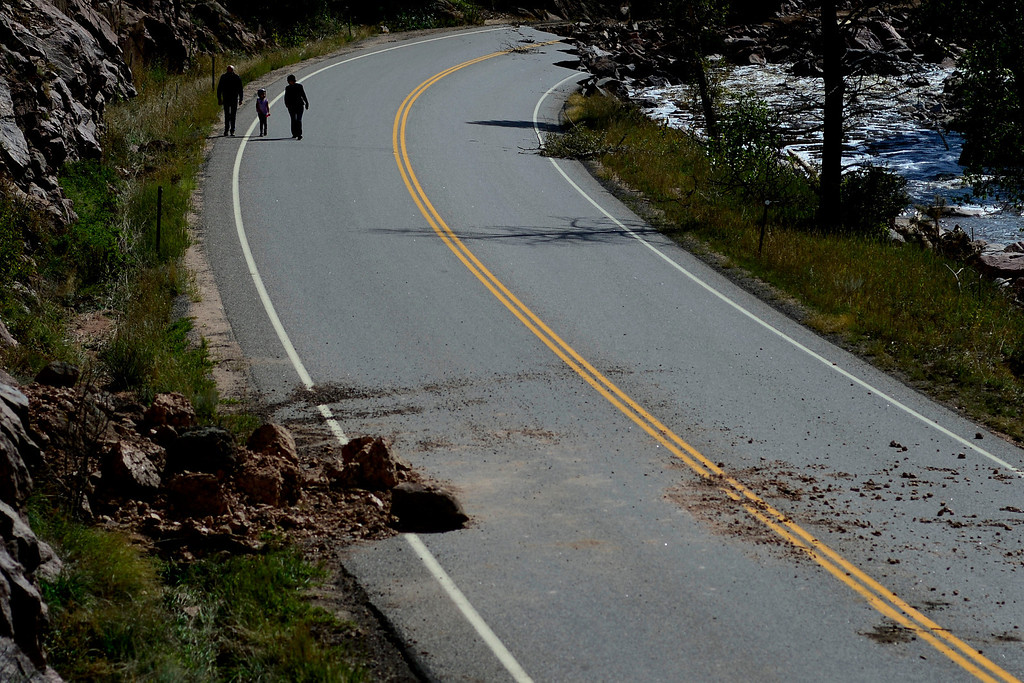 . PINEWOOD SPRINGS, CO - SEPTEMBER 22: Pinewood Springs resident Dick Hodges walks with his daughter, Emma Hodges, and granddaughter, Nina Pabst, 6, in order to get out of town during a tour to look at the damage caused by recent flooding in the area on U.S. Highway 36 between Lyons and Pinewood Springs. Large sections of the roadway are completely missing, while others are severely damaged making travel impossible by way of motor vehicle in spots. (Photo by AAron Ontiveroz/The Denver Post)