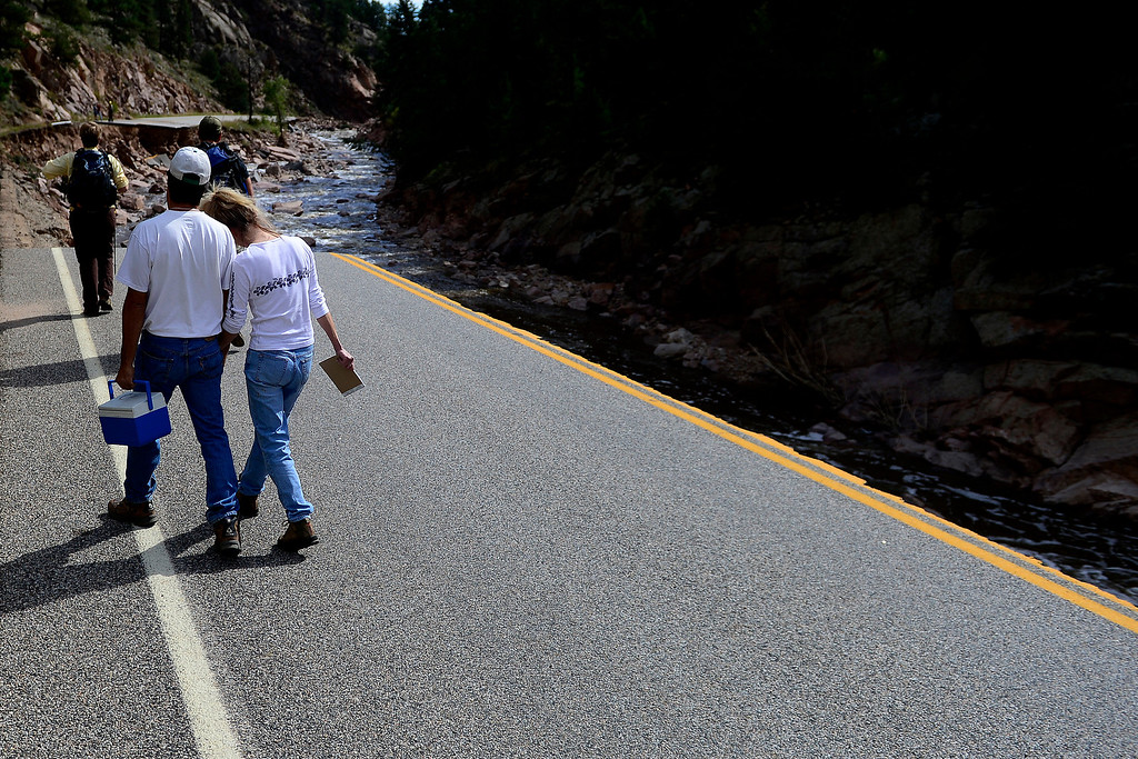 . PINEWOOD SPRINGS, CO - SEPTEMBER 22: Denise Stewart lays her head on John Lucero\'s shoulder as they walk back towards Pinewood Springs during a tour to look at the damage caused by recent flooding in the area on U.S. Highway 36 between Lyons and Pinewood Springs. Pavement is missing in many section of the road that connects Lyons to Estes Park. (Photo by AAron Ontiveroz/The Denver Post)