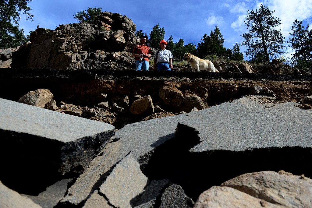 . PINEWOOD SPRINGS, CO - SEPTEMBER 22: CDOT executive director Don Hunt (center) stands with his dog, Sasha, and resident Forrest Snider during a tour to look at the damage caused by recent flooding in the area on U.S. Highway 36 between Lyons and Pinewood Springs. Pavement is missing in many section of the road that connects Lyons to Estes Park. (Photo by AAron Ontiveroz/The Denver Post)