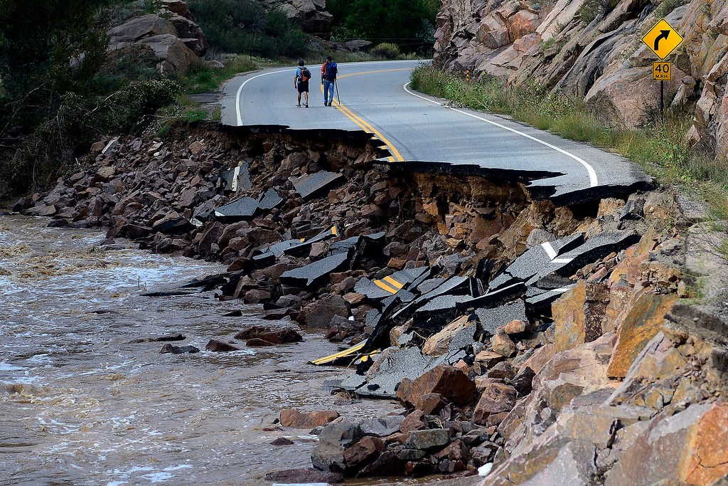 . PINEWOOD SPRINGS, CO - SEPTEMBER 22: Hikers Forrest Snider (right) and Joe Rowinski make their way up the canyon during a tour to look at the damage caused by recent flooding in the area on U.S. Highway 36 between Lyons and Pinewood Springs. Large sections of the roadway are completely missing, while others are severely damaged making travel impossible by way of motor vehicle in spots. (Photo by AAron Ontiveroz/The Denver Post)