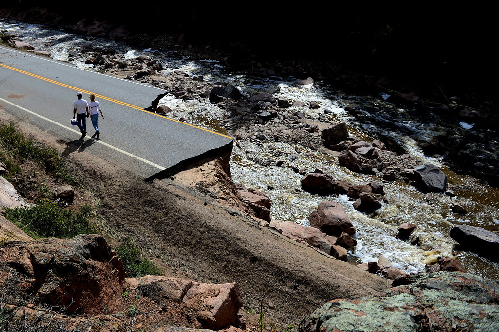 . PINEWOOD SPRINGS, CO - SEPTEMBER 22: Denise Stewart holds hands with John Lucero as they walk back towards Pinewood Springs during a tour to look at the damage caused by recent flooding in the area on U.S. Highway 36 between Lyons and Pinewood Springs. Pavement is missing in many section of the road that connects Lyons to Estes Park. (Photo by AAron Ontiveroz/The Denver Post)