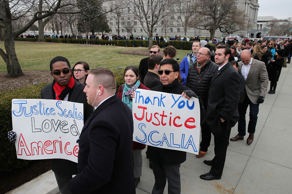 . People hold signs of thanks and support while waiting in line to pay their respects to U.S. Supreme Court Associate Justice Antonin Scalia outside the court\'s building February 19, 2016 in Washington, DC. Justice Scalia will lie in repose in the Great Hall of the high court where visitors will pay their respects.  (Photo by Chip Somodevilla/Getty Images)