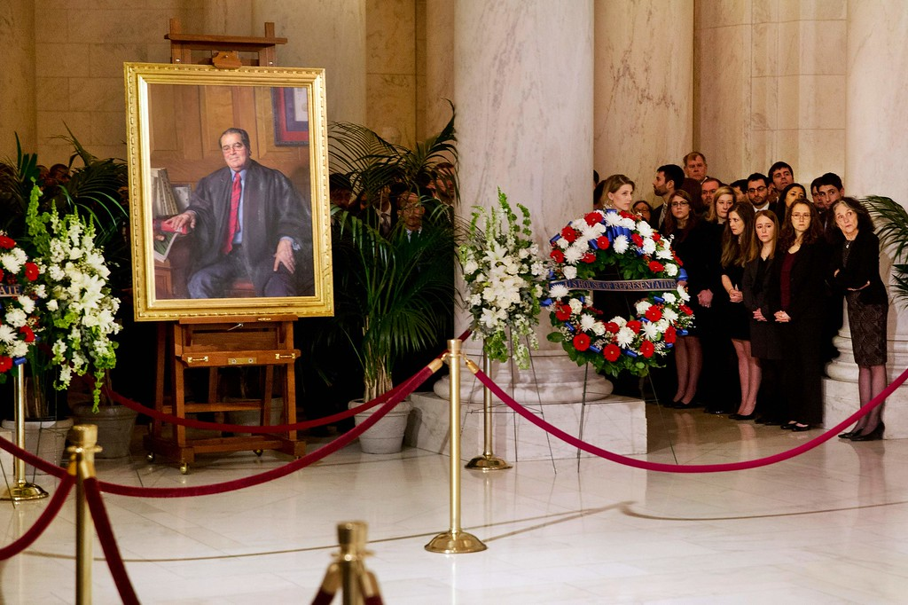 . Law clerks and Supreme Court staff watch a private ceremony in the Great Hall of the Supreme Court where late Supreme Court Justice Antonin Scalia (portrait L) lies in repose in Washington, DC,  on February 19, 2016. At left is a portrait of Scalia.  / AFP / POOL / Jacquelyn  MARTIN/AFP/Getty Images