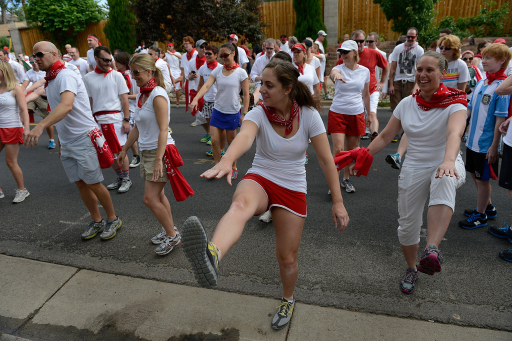 . DENVER, CO - JULY 13: Runners stretch at the start line at the third annual Highland Running of the Bulls one-mile race in the Highland neighborhood in Denver Colorado Saturday morning, July 13, 2013. Inspired by the running of the bulls in Pamplona Spain, runners get chased through the course by the Rocky Mountain Rollergirls wielding foam and plastic bats, proceeds from the race benefit the Tennyson Center for Children whose aim is to �work with children, youth, and their families to overcome a variety of life crises, including abuse and neglect.� (Photo By Andy Cross/The Denver Post)