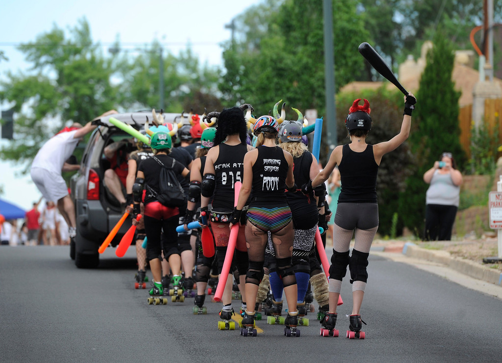. DENVER, CO - JULY 13:  The Rocky Mountain Rollergirls arrive, via a tow, for the third annual Highland Running of the Bulls one-mile race in the Highland neighborhood in Denver Colorado Saturday morning, July 13, 2013. Inspired by the running of the bulls in Pamplona Spain, runners get chased through the course by the Rocky Mountain Rollergirls wielding foam and plastic bats, proceeds from the race benefit the Tennyson Center for Children whose aim is to �work with children, youth, and their families to overcome a variety of life crises, including abuse and neglect.� (Photo By Andy Cross/The Denver Post)