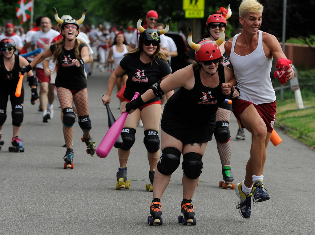 . DENVER, CO - JULY 13: A runner gets hit by a Rocky Mountain Rollergirl during the third annual Highland Running of the Bulls one-mile race in the Highland neighborhood in Denver Colorado Saturday morning, July 13, 2013. Inspired by the running of the bulls in Pamplona Spain, runners get chased through the course by the Rocky Mountain Rollergirls wielding foam and plastic bats, proceeds from the race benefit the Tennyson Center for Children whose aim is to �work with children, youth, and their families to overcome a variety of life crises, including abuse and neglect.� (Photo By Andy Cross/The Denver Post)