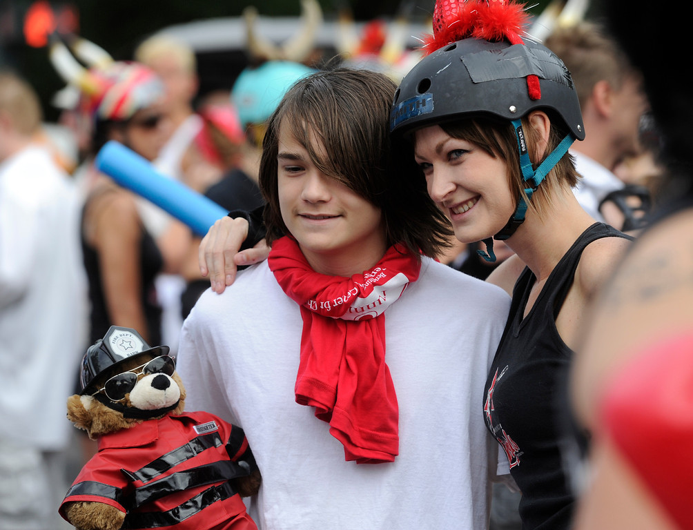 . DENVER, CO - JULY 13: Runner, David Dawson, 13, left, has his picture taken with Rocky Mountain Rollergirl, Jill �Sissy Rinkshaw� Montgomery at the start of the third annual Highland Running of the Bulls one-mile race in the Highland neighborhood in Denver Colorado Saturday morning, July 13, 2013. Inspired by the running of the bulls in Pamplona Spain, runners get chased through the course by the Rocky Mountain Rollergirls wielding foam and plastic bats, proceeds from the race benefit the Tennyson Center for Children whose aim is to �work with children, youth, and their families to overcome a variety of life crises, including abuse and neglect.� (Photo By Andy Cross/The Denver Post)