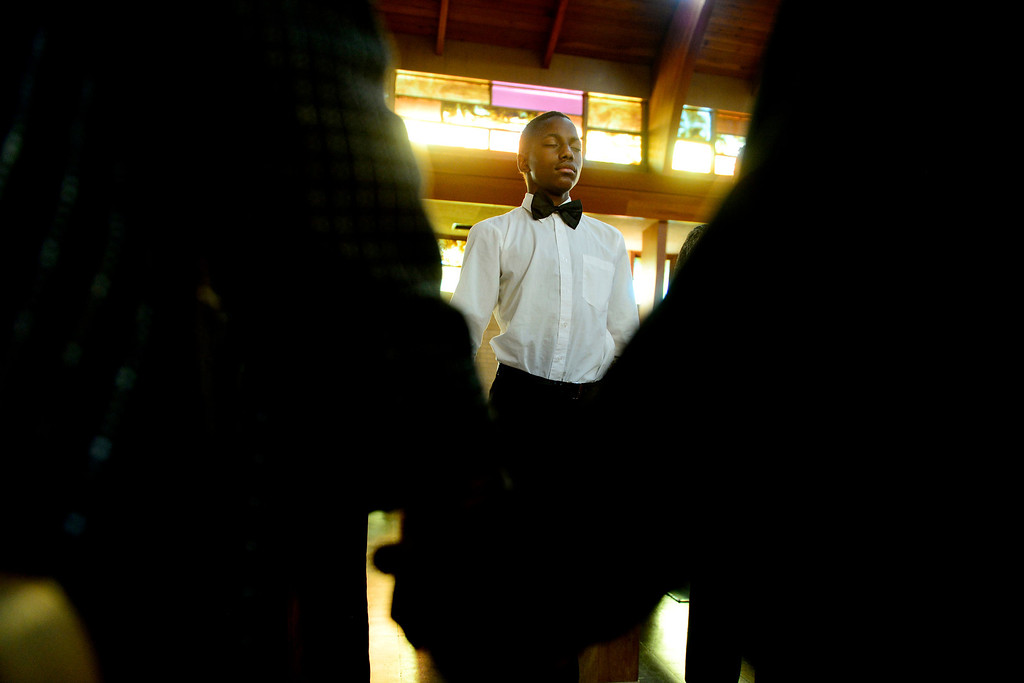 . Dererl Burton, 15, prays with the parish following the Sunday service at Macedonia Baptist church in Denver on November 24, 2013. Pastor Victor-LaMonte Lane was installed as the new pastor of the church on December 6, 2013. (Photo by AAron Ontiveroz/The Denver Post)