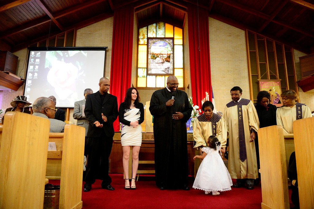 . Pastor Victor-LaMonte Lane performs a blessing on Tatyianna Skyy Parrish during the Sunday service at Macedonia Baptist church in Denver on November 24, 2013. Lane was officially installed as the new pastor of the church on December 6, 2013. (Photo by AAron Ontiveroz/The Denver Post)