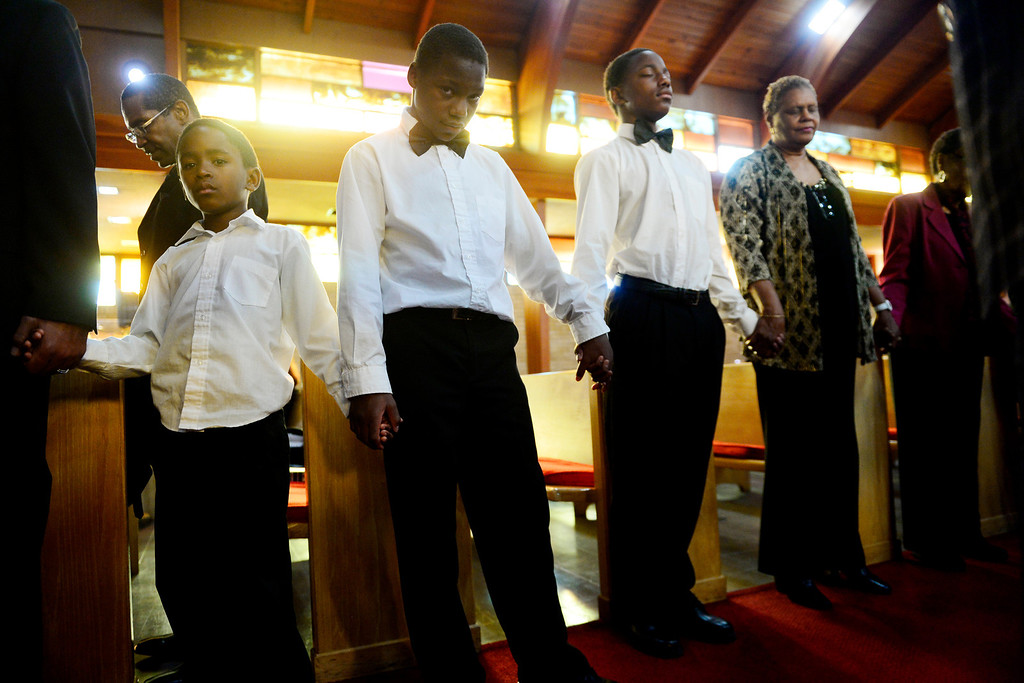. Xavier Kimbrough, 8, Ta\'yon Burton, 12, and Dererl Burton, 15, pray with the parish following the Sunday service at Macedonia Baptist church on November 24, 2013. Pastor Victor-LaMonte Lane was installed as the new pastor of Macedonia Baptist church in Denver on December 6, 2013. (Photo by AAron Ontiveroz/The Denver Post)