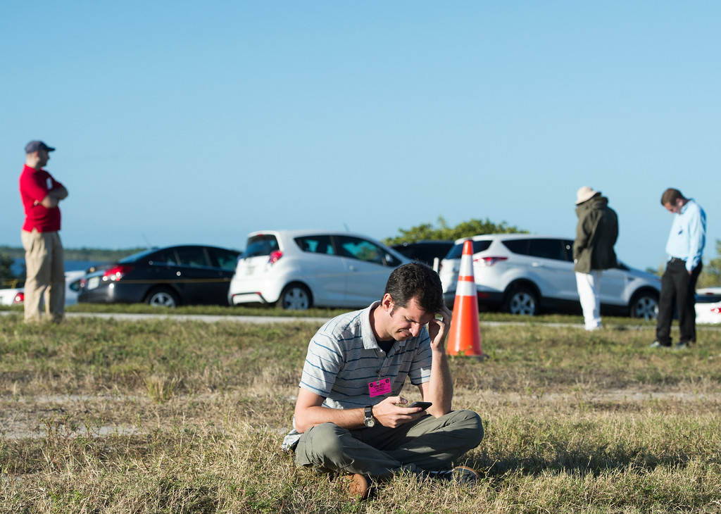. John Brack looks at his phone while waiting for the hold for the launch of Orion to be lifted Thursday, December 4, 2014 at the Cape Canaveral Air Force Station in Cape Canaveral, Florida. Orion fitted with United Launch Alliance\'s Delta IV Heavy rocket scrubbed the first day of flight window after a possible issue with the valve systems on the boosters. (Photo By Brent Lewis/The Denver Post)