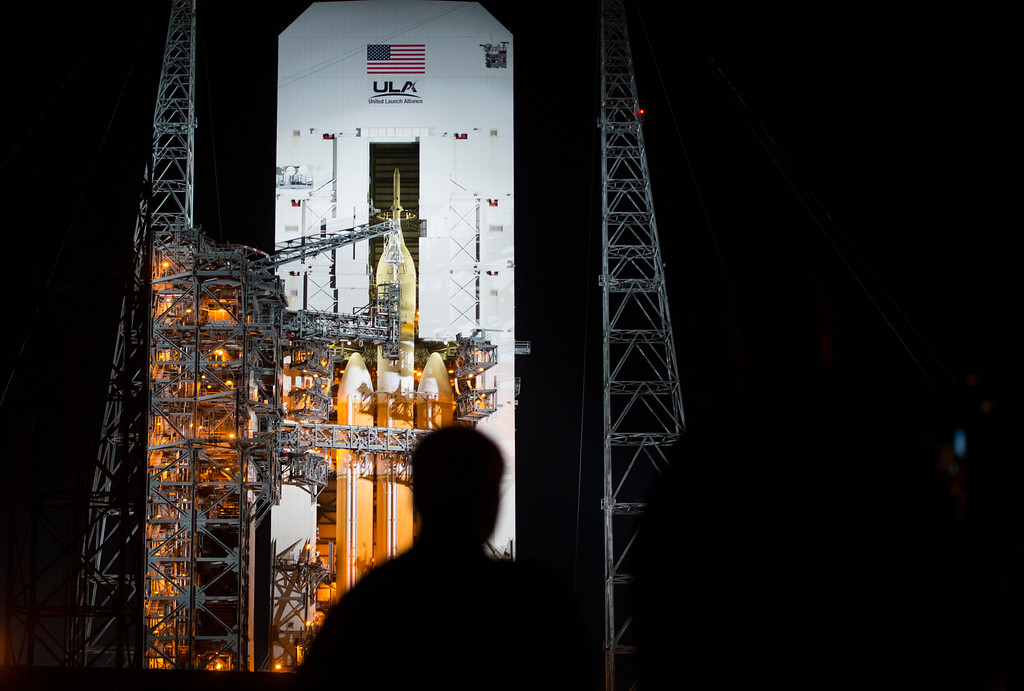 . Members of the media watch the spacecraft Orion as it begins to emerge from the Mobile Service Tower as it rolls away Wednesday, December 3, 2014 at Space Launch Complex 37 at the Kennedy Space Center in Cape Canaveral, Florida. Orion fitted with a United Launch Alliance Delta IV Heavy rocket prepares to travel into space on the first test flight of the Orion missions which hope to some day place a man on Mars.  (Photo By Brent Lewis/The Denver Post)