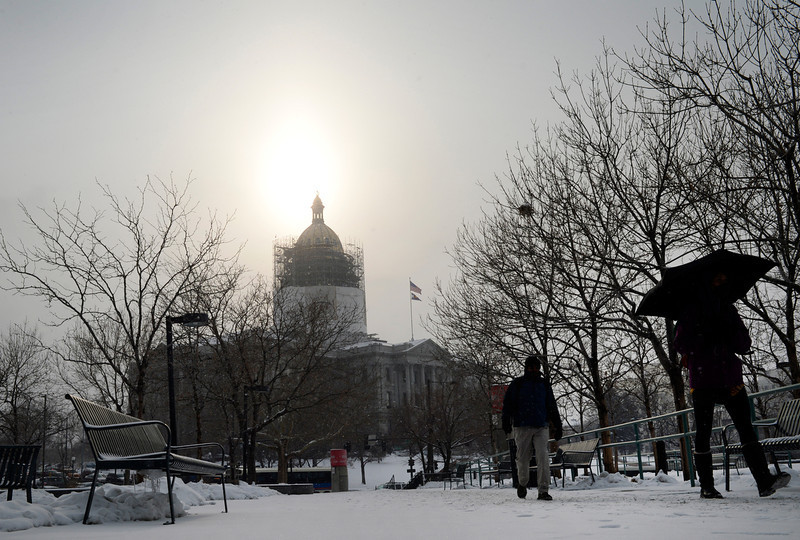 . Pedestrians make their way across the RTD Plaza near Broadway and Colfax in a light snow Tuesday morning, February 04, 2014. (Photo By Andy Cross / The Denver Post)