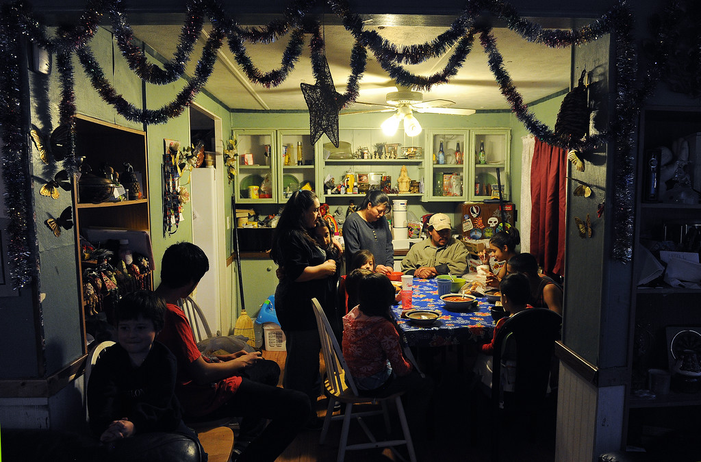. GREELEY, CO - DECEMBER 16, 2013:  Norma Meza hugs her daughter Maria, 11, as Rosario Moreno, standing, and her husband Jose, seated, join some of the kids for dinner at the Meza\'s tiny home in Greeley, CO on December 16, 2013. The children seated at the table are from far right  clockwise:  Genoveva Meza, 14, Martin Meza jr., 17, Sergio Meza, 3, Janeth Moreno, 10, Edwin Moreno, 2, Yanna Moreno, 8.  At left are brothers Jared, 5, and Ivan, 18, Moreno. The Meza family, which consists of four children, Norma and her husband Martin have taken in the Moreno family after they lost everything in the September floods.  Rosario and her husband Jose have 5 children and are without a home at the moment.  Norma says she will help out her best friend for as long as she needs to.  The tiny house has 3 bedrooms and 2 small bathrooms and is home now to 14 people, 2 cats and 3 dogs.  (Photo By Helen H. Richardson/ The Denver Post)