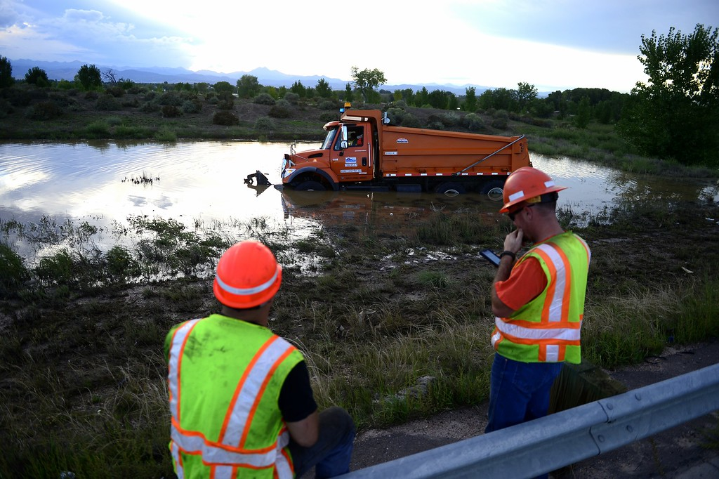 . LONGMONT, CO - SEPTEMBER 17: A CDOT truck is submerged in water after blowing a tire and driving off road into a pool of flood water. CDOT employees on the scene provided no further information. (Photo by AAron Ontiveroz/The Denver Post