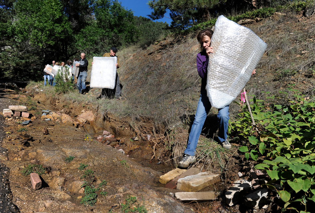 . BOULDER, CO - Sept. 28: With Ellen Greenhouse leading the way, the group carefully crosses a culvert using two stones as a bridge. Friends and fellow Boulder artists gather to hike in to the home and studio of artist Marco Montanari to rescue and carry out his Encaustic paintings that need to be packed and sent to New York for a show in November. Montanari\'s home and studio did not suffer damage in the floods, but all roads leading in and out had been impassable up until just a few days ago. The group was able to drive a short distance up Wagon Wheel Gap Road and hiked the rest of the way in and out. (Photo By Kathryn Scott Osler/The Denver Post)