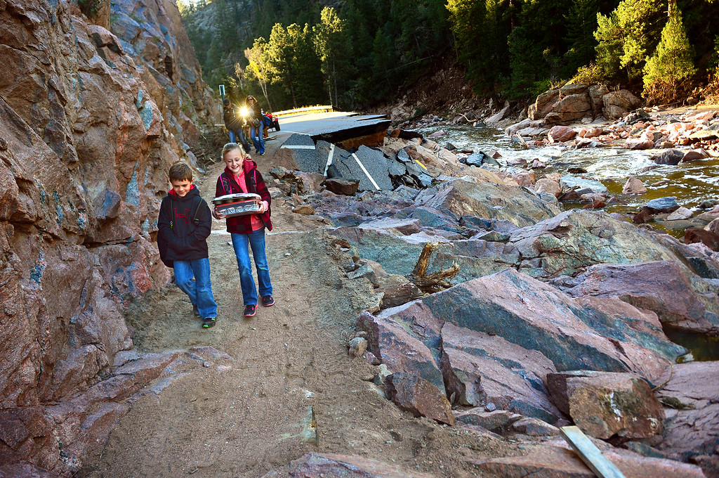 . Kody Payne, 7, and his sister Kaelyn, 10, walk along a dirt path next to what used to be U.S. 36 near Pinewood Springs, Colo. on Sept. 24, 2013. The siblings were heading back to Estes Park Elementary School for the first time since floods damaged the town. Kaelyn carries trays of cupcakes to celebrate her 10th birthday, while their parents, Judd and Sherami, walk behind them. The community of Pinewood Springs was left an island after the massive flood took out all major roads and bridges. Residents, who refused to evacuate, worked aggressively to make this path for access to Estes Park. They park their cars at Elk Meadows, above the damaged highway, then make the trek back and forth to cars on the other side to get home. The walk is about a mile.