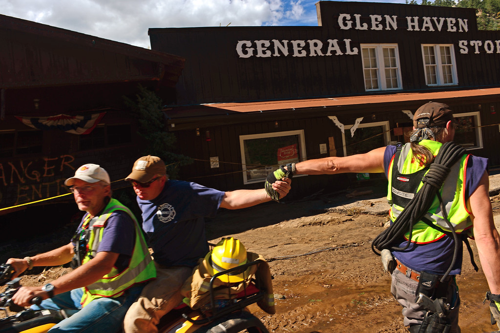 . GLEN HAVEN, CO - SEPTEMBER 17:  Glen Haven Fire Captain Tom Housewright high fives a fellow firefighter as the two cross on main street of Glen Haven, CO on September 17, 2013. (Driving the ATV is firefighter Clifton DeWitt.) The small mountain town of Glen Haven north east of Estes Park has been wiped out by the recent and massive flooding. (Photo By Helen H. Richardson/ The Denver Post)
