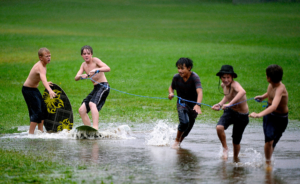 . BOULDER, CO. - SEPTEMBER12:  A group of kids use a flooded field for skim-boarding at North Boulder Park in Boulder, Colo. on September 12, 2013. Record-breaking rain turned normally quiet creeks into raging, brown torrents that swept through Boulder, flooding homes, swamping cars and closing roads and schools. (Photo By Craig F. Walker / The Denver Post)