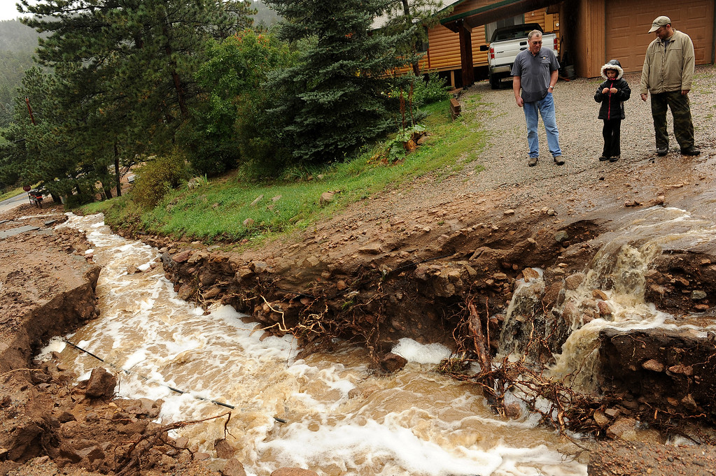 . RAYMOND , CO - SEPTEMBER 12: Homeowner Brad DeHaan, right, with his daughter, Elise, 8, and neighbor Kevin Duffy, check out the flooding damage to the road that leads to their houses on Conifer Hill Road in the roadside community of Riverside, about 12 miles west of Lyons, Colo. along Highway 7 on September 12, 2013.  Heavy and continuous rains have created devastating and major flooding in many mountain communities. Some areas have had over 10 inches of rain in the last 24-48 hours.  (Photo By Helen H. Richardson/ The Denver Post)