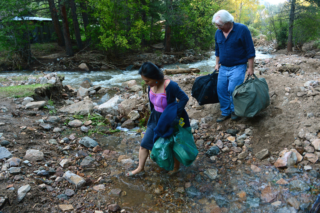 . LEFTHAND CANYON, CO - SEPTEMBER 19: Lefthand Canyon residents Scott Peoples, right, and his wife Hyung Joo Kim ford a small stream along a path next to Lefthand Creek in Lefthand Canyon Drive west of Boulder, Co on September 19, 2013 . The couple, after having stayed four days during the floods, then getting evacuated by helicopter, decided they wanted to move back into their home. Despite the fact that they are cut off on both ends of the canyon as the roads are destroyed, they would rather be at home than in a hotel or with friends. They have cars on both ends of the destroyed bridges and are able to get home as well as get to town and to work. They have a generator for electricity and their home phone works but they don\'t have running water. (Photo By Helen H. Richardson/ The Denver Post)