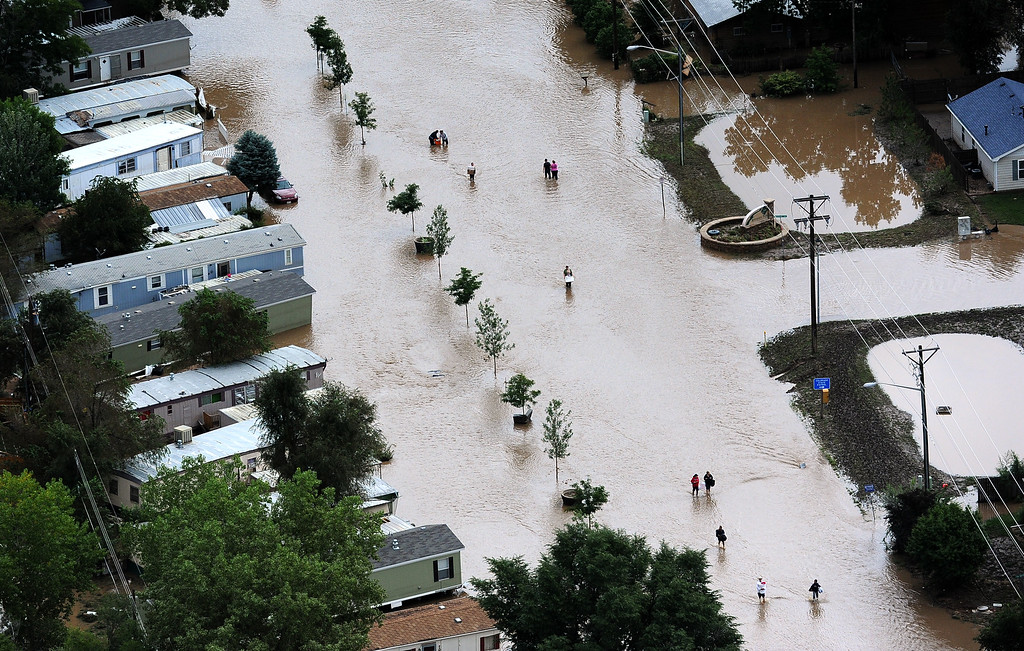 . EVANS, CO. - SEPTEMBER 16:  People walk down 37th street in Evans, Colorado, carrying belongings recovered from flooded  homes in the area. Aerial photographs of the Platte River flooding cities and farms in Weld County Colorado. (Photo By Tim Rasmussen/The Denver Post)