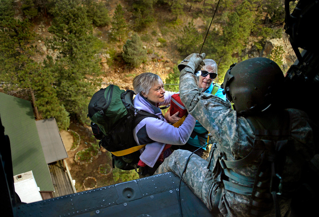 . Sgt. 1st Class Keith Bart, based in Fort Carson, hoists two women aboard a UH-60 Black Hawk during a rescue near Jamestown on Sept. 17, 2013. Bart noticed the women as they waved red scarves from the deck of a home. State officials estimated about 600 people were still stranded in isolated areas.