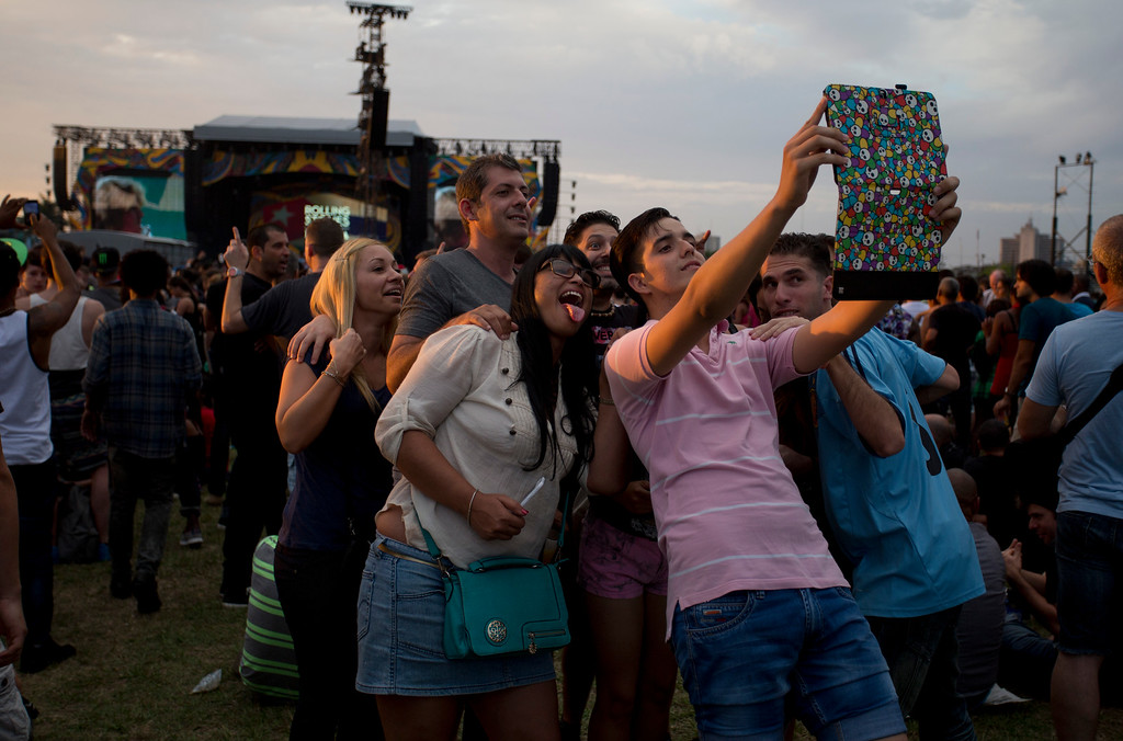 . Spectators take a selfie as they wait for the beginning of the Rolling Stones concert in Havana, Cuba, Friday March 25, 2016. The Stones are performing in a free concert in Havana Friday, becoming the most famous act to play Cuba since its 1959 revolution. (AP Photo/Desmond Boylan)
