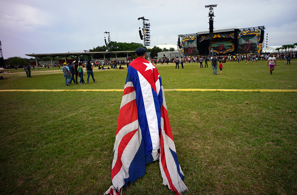 . A fan walks carrying the Cuban and the UK flags draped on his back, at the venue where the Rolling Stones will play their concert in Havana, Cuba, Friday, March 25, 2016. The Stones are performing in a free concert in Havana, becoming the most famous act to play Cuba since its 1959 revolution.(AP Photo/Ramon Espinosa)
