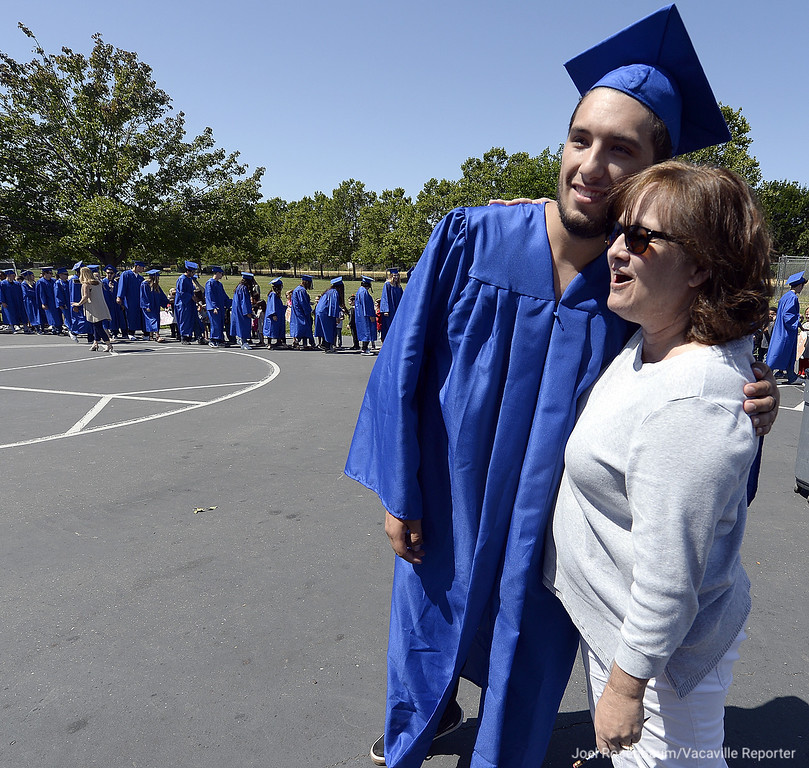 . As his fellow graduates parade around the campus at Callison Elementary School, Anthony DuClair a graduating senior poses for a picture with Leslie Losberger who was his first grade teacher when he attended the school. Joel Rosenbaum -- The Reporter