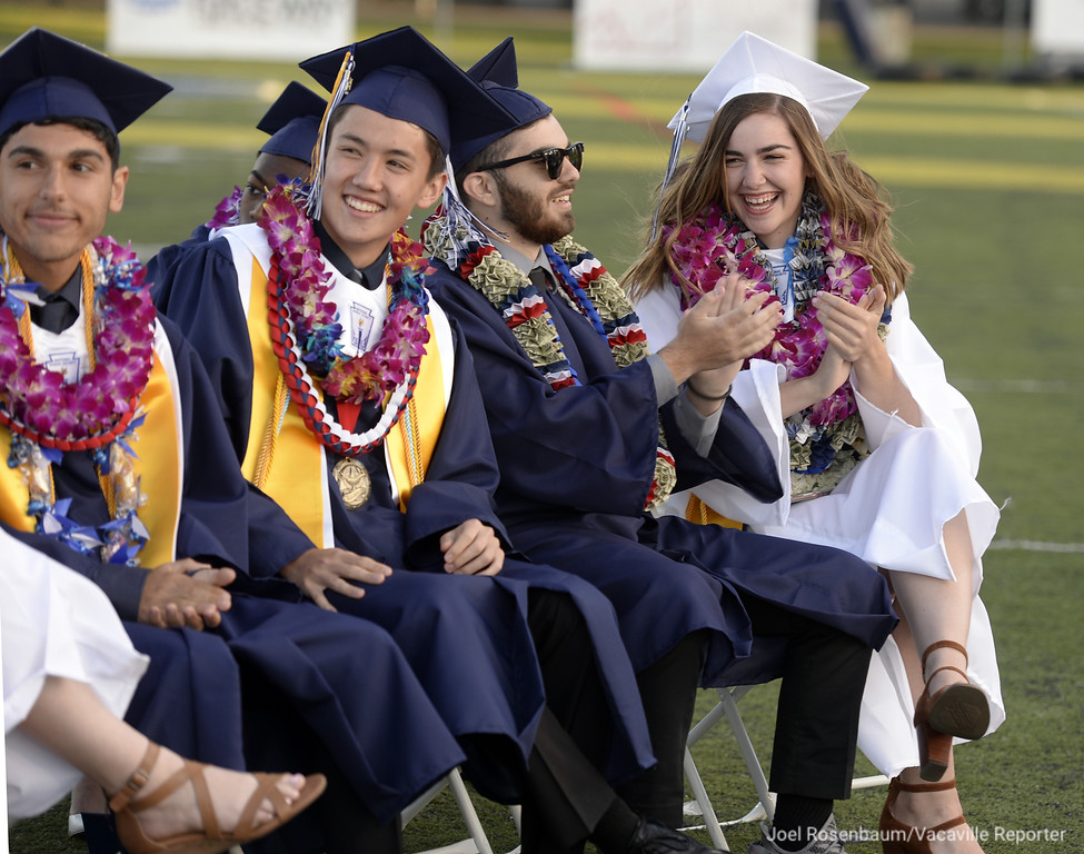 . Vacaville Christian High graduate, Alexander Foley (left,) Jack Gardner (second from left,) Cruz Gomez and Elyse Gottschall laugh together during commencement ceremonies on Thursday at Falcon Field.