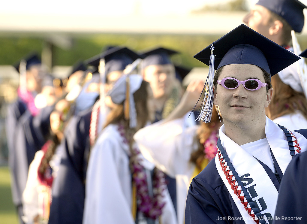 . Wearing a pair of novelty sunglasses, Joshua Spinardi hams it up while waiting in line with his fellow classmates before marching in procession to being commencement ceremonies Thursday at Falcon Field at Vaca Christian.