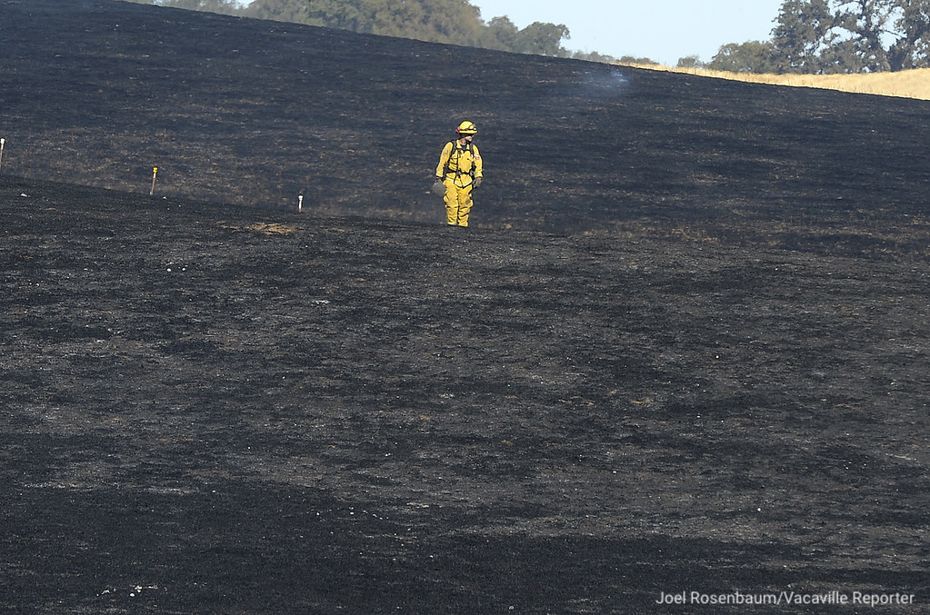 . A firefighter from the California Department of Forestry and Fire Protection (CAL FIRE) checks for hot spots of a 96 acre four-alarm grass fire off Olivas Lane in English Hills  Joel Rosenbaum -- The Reporter