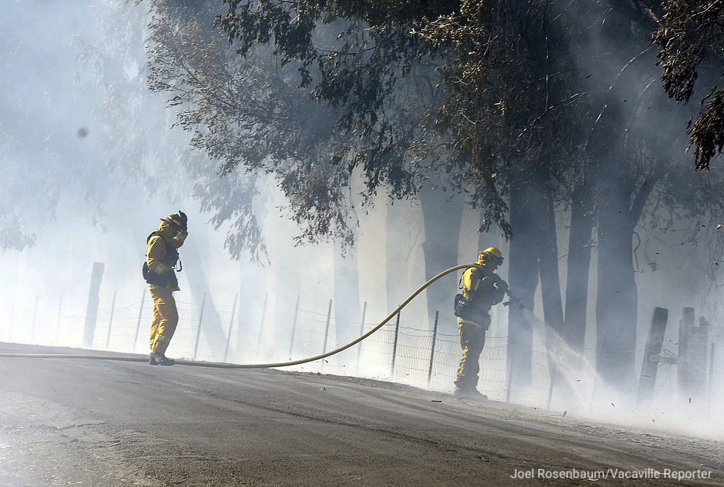 . Vacaville Fire Department firefighters attack a hot spot along a fence of a home along Olivas Lane Monday in the rural Vacaville neighborhood of English Hills. Crews from throughout Solano County and the California Department of Forestry and Fire Protection (CAL FIRE) battled the blaze and are still investigating the cause.  Joel Rosenbaum -- The Reporter