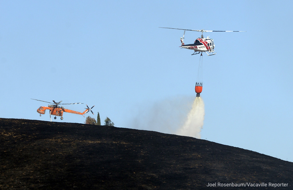 . CAL FIRE Helicopter 104 makes a water drop on a hot spot on a portion of a fast moving grass fire Monday along Olivas Lane in the rural Vacaville neighborhood of English Hills as a s a Sikorsky S-64 Skycrane also prepares to a make a drop. Joel Rosenbaum -- The Reporter