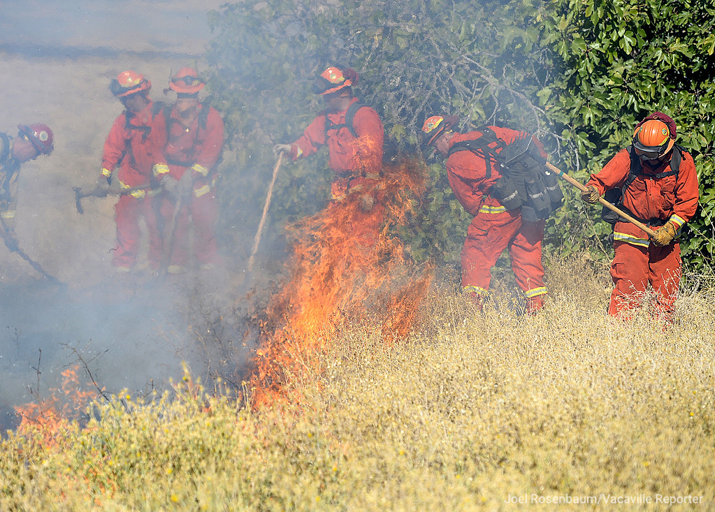 . An inmate hand crew from the CAL FIRE Delta Camp make an attack on a flare up from a fast moving grass fire Monday along Olivas Lane in the rural Vacaville neighborhood of English Hills that burned more than 90 acres. Joel Rosenbaum -- The Reporter