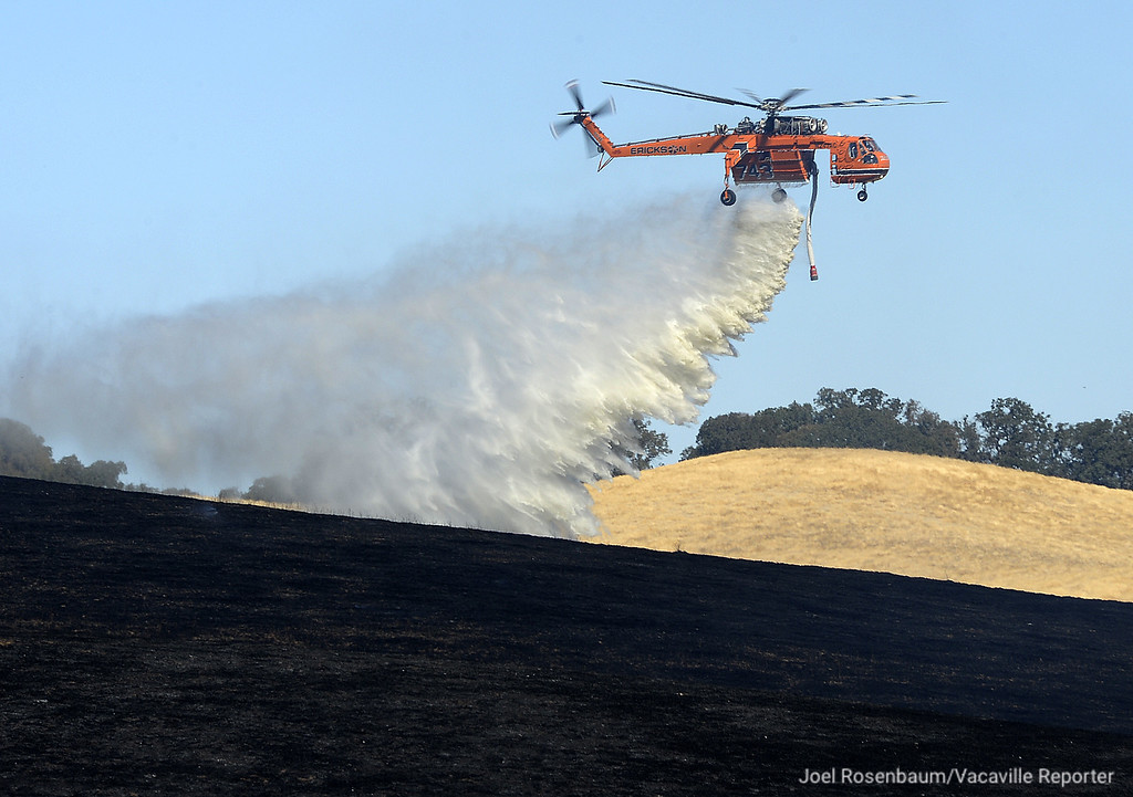 . A Sikorsky S-64 Skycrane makes a water drop on a hot spot on a portion of a grass fire that swept through English Hills area of rural Vacaville Monday morning burning more than 90 acres. Joel Rosenbaum -- The Reporter